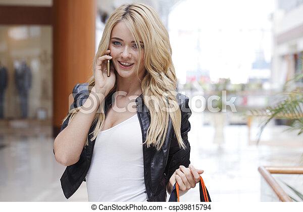 Una mujer de compras hablando por teléfono - csp39815794