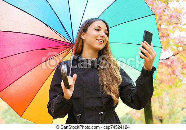 mujer, debajo, arco irirs, teléfono, teniendo paraguas, elegante, outdoors., hermoso, joven, otoño - csp74524124