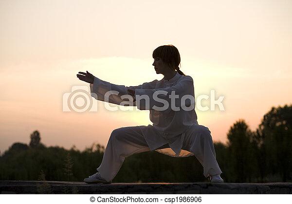 La mujer de traje blanco hace el ejercicio taiji chuan - csp1986906