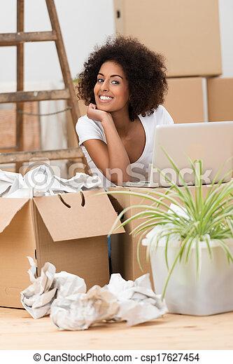 Una mujer desempacando cajas en su nueva casa - csp17627454