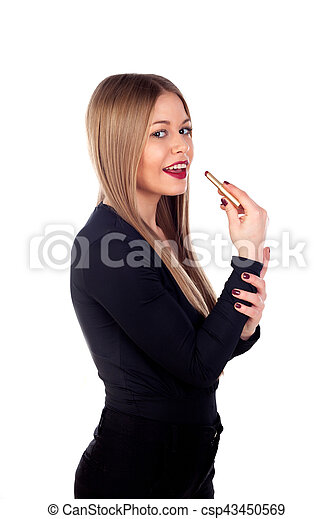 Una joven de moda pintando sus labios - csp43450569