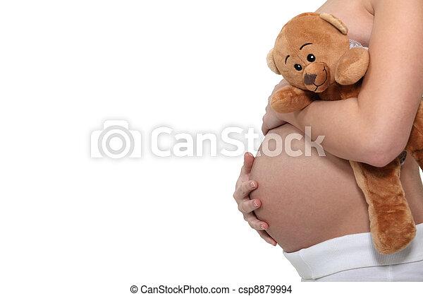 Mujer embarazada sosteniendo un oso de peluche - csp8879994