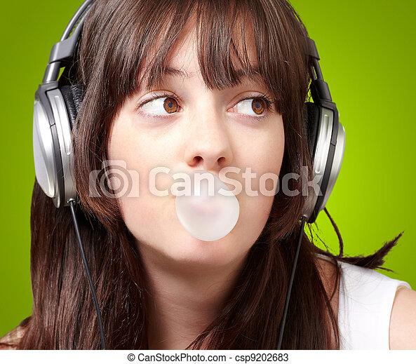 Retrato de jovencita escuchando música con chicle sobre verde - csp9202683