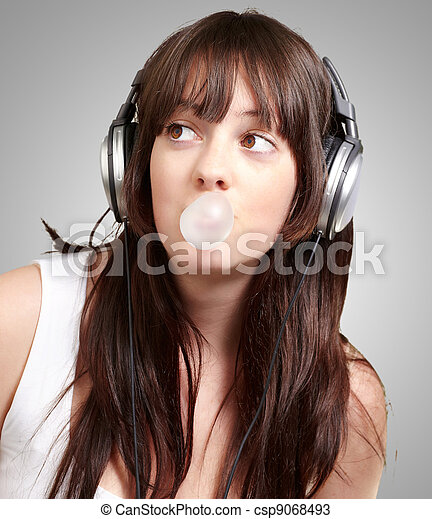 Retrato de jovencita escuchando música con chicle sobre fondo gris - csp9068493