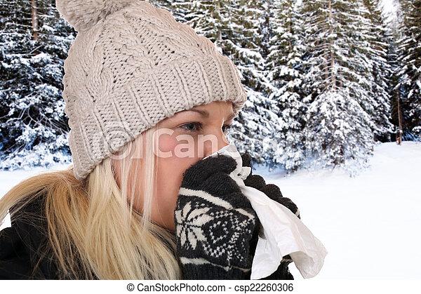 Una joven con un virus de gripe que estornuda en un tejido - csp22260306