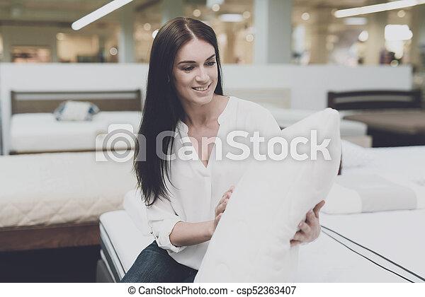Una mujer escoge una almohada en una gran tienda. Se sienta en la cama y la examina. Se sienta y la examina - csp52363407