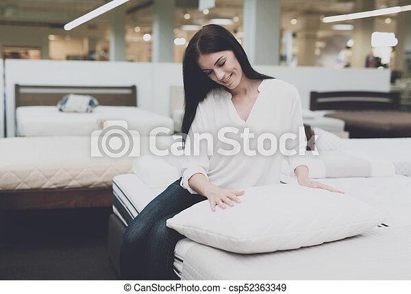 Una mujer escoge una almohada en una gran tienda. Se sienta en la cama y la examina. Se sienta y la examina - csp52363349