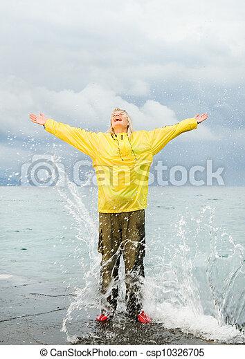 Una joven feliz cerca del océano en la tormenta - csp10326705