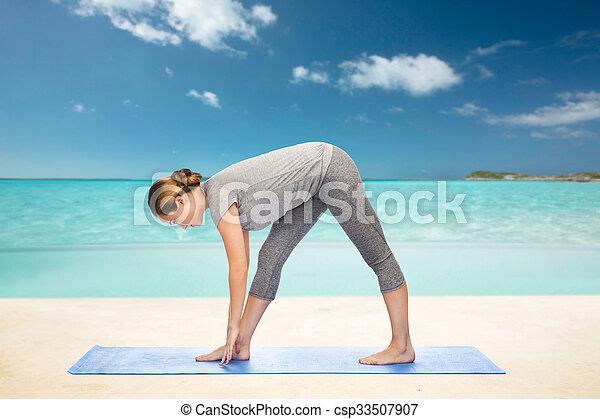 Mujer haciendo yoga intensa postura estirada en la alfombra - csp33507907