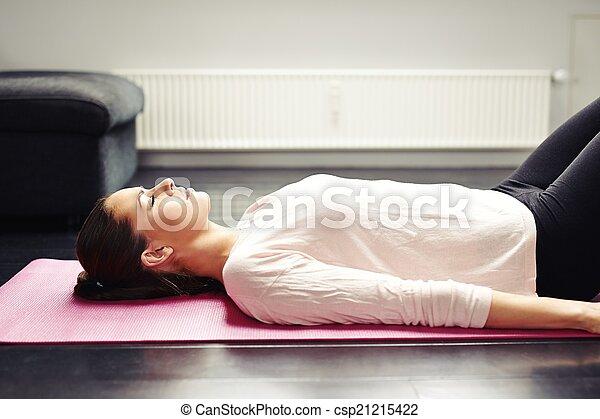 una joven atractiva relajándose en una alfombra de yoga