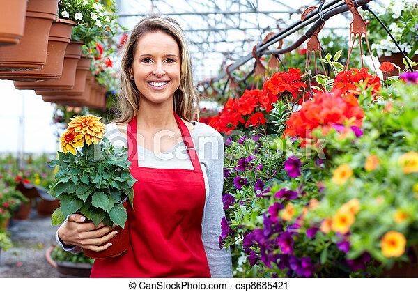 Una florista que trabaja en una tienda de flores. - csp8685421
