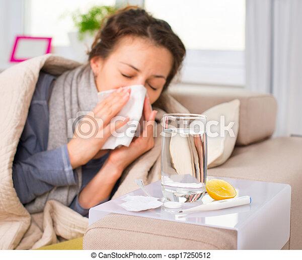 Mujer enferma. Gripe. Una mujer se resfrió. Estornudando en tejido - csp17250512