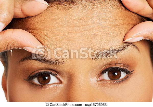 Una mujer mirando sus arrugas en la frente - csp15726968
