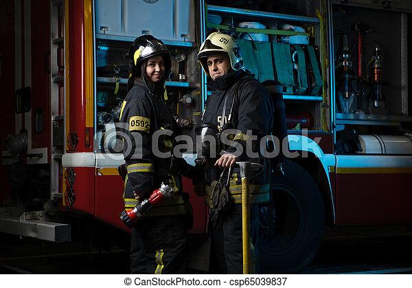 Foto de hombre y mujer bombero en el camión de bomberos - csp65039837