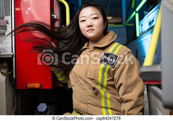 Foto de mujer bombero en el fondo del camión de bomberos - csp64247278