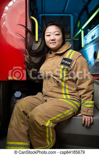 Imágenes de mujer bombero en el fondo del camión de bomberos - csp64185679