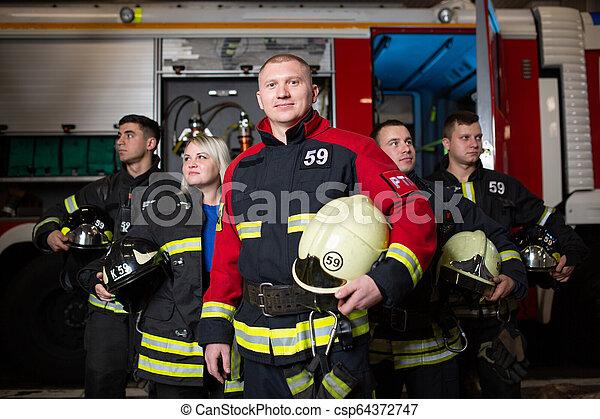 Imágenes de cuatro bomberos y mujeres en el fondo del camión de bomberos - csp64372747