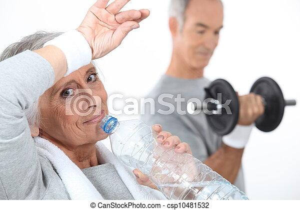 Mujer mayor bebiendo agua después de la sesión de gimnasia - csp10481532
