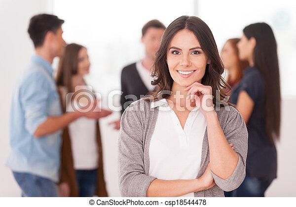 Es una líder de equipo. Una joven confiada sosteniendo la mano en la barbilla y sonriendo mientras un grupo de personas se comunican en el fondo - csp18544478