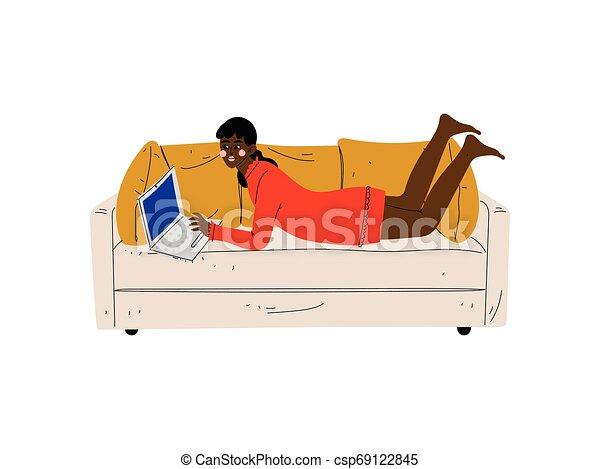 Una chica hermosa en el sofá con portátil, una joven afroamericana trabajando o relajándose en casa usando ilustraciones de vectores de computadora - csp69122845