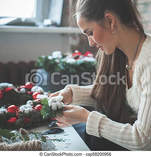 Hermosa mujer haciendo decoraciones navideñas en casa - csp58200956