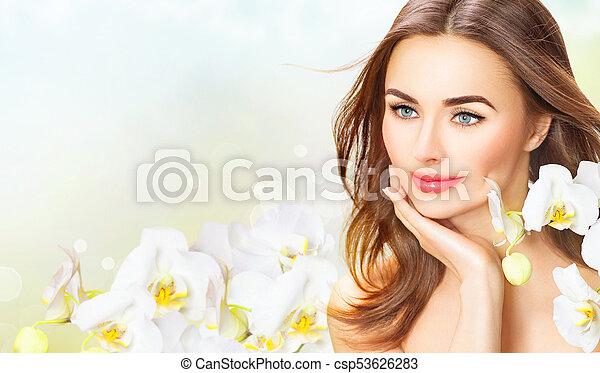 Mujer hermosa con flores de orquídea. Hermosa chica del spa tocando su cara - csp53626283