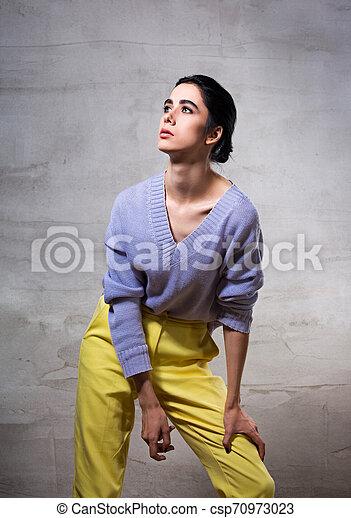 Hermosa Mujer Pensante De Moda Posando Y Mirando Hacia Arriba En Sueter Violeta Y Pantalones Amarillos En El Fondo Del Canstock