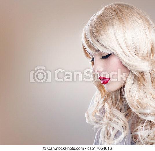 Retrato de mujer rubia. Hermosa chica rubia con el pelo largo ondulado - csp17054616