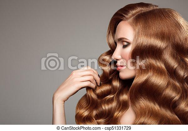 Retrato de mujer con cabello rizado largo y hermoso pelirrojo. - csp51331729