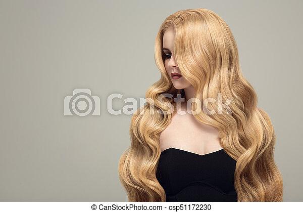 Mujer rubia con cabello largo y rizado. - csp51172230