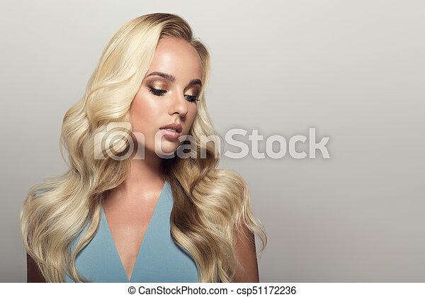 Mujer rubia con cabello largo y rizado. - csp51172236