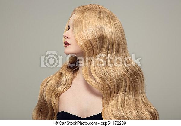 Mujer rubia con cabello largo y rizado. - csp51172239