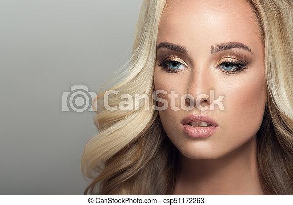 Mujer rubia con cabello largo y rizado. - csp51172263