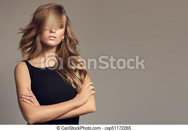 Mujer rubia con cabello largo y rizado. - csp51172265