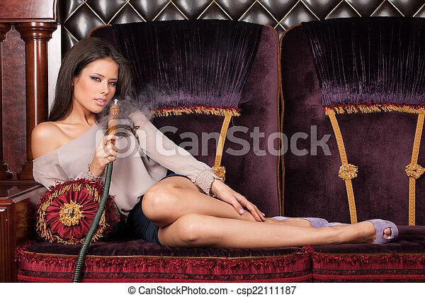 mujer hermosa, seductor, joven, conmovedor, fumar, sexy, niña, piernas, acostado, hookah. - csp22111187