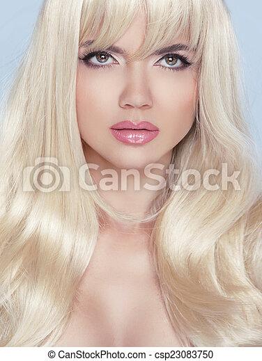Mira. Maquillaje. Hermosa mujer rubia con el pelo largo ondulado. - csp23083750