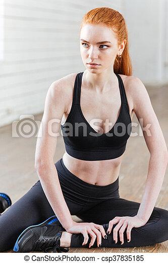 Una joven mujer en forma estirada en el gimnasio - csp37835185