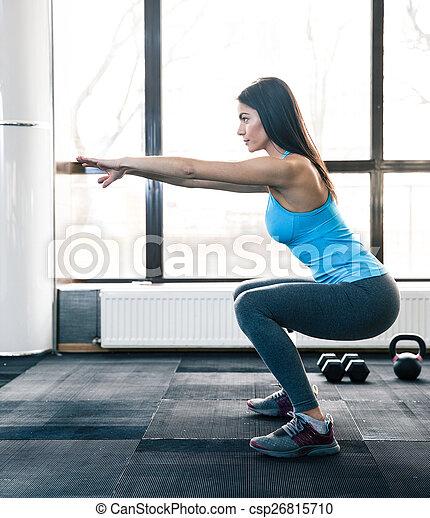 Mujer joven haciendo sentadillas - csp26815710