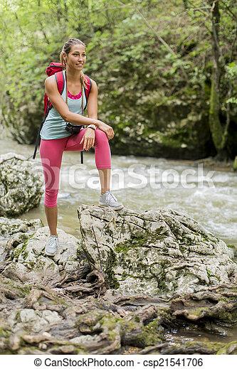 Una joven senderismo en el bosque - csp21541706