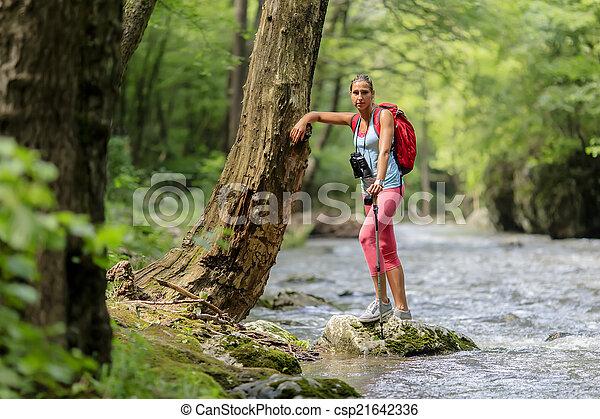 Una joven senderismo en el bosque - csp21642336