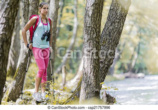 Una joven senderismo en el bosque - csp21757996