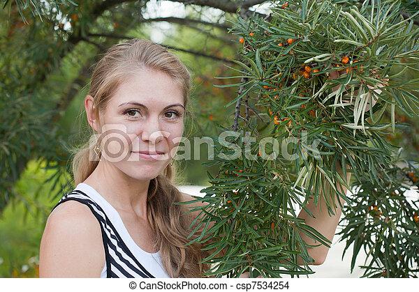 Una joven cerca de un arbusto de bayas marinas con frutas - csp7534254