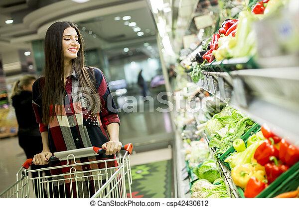 Una mujer joven en el supermercado - csp42430612