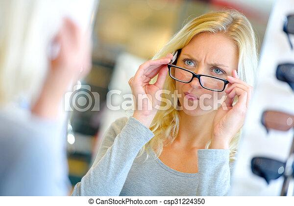 Una mujer eligiendo gafas - csp31224350
