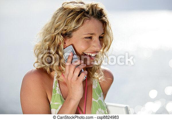 Mujer rubia haciendo llamadas en la playa - csp8824983