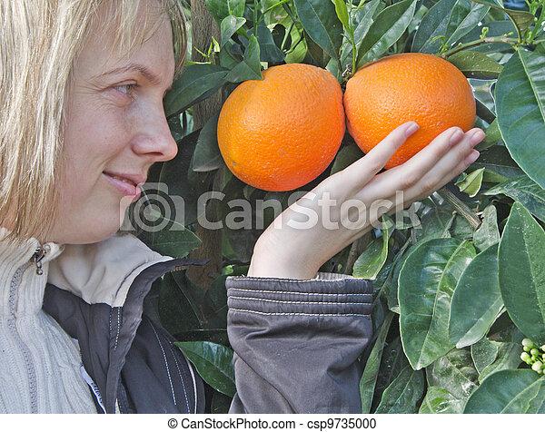 Mujer sosteniendo naranjas maduras - csp9735000