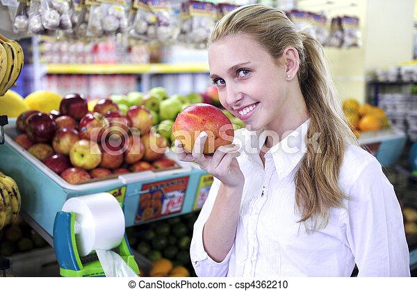 Una mujer oliendo un mango en el supermercado - csp4362210