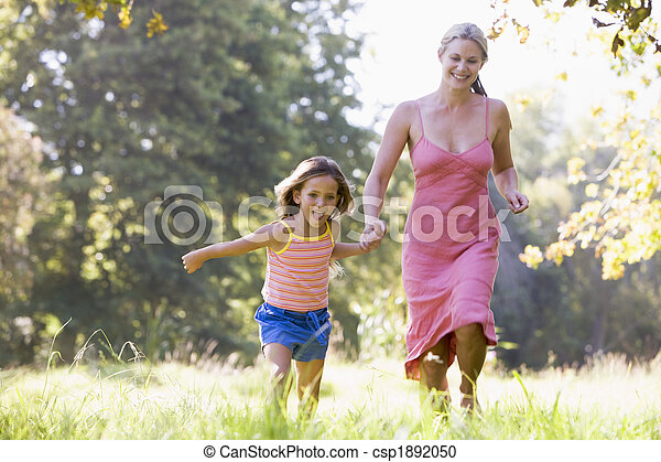 Mujer y joven corriendo al aire libre sosteniendo sus manos y sonriendo - csp1892050