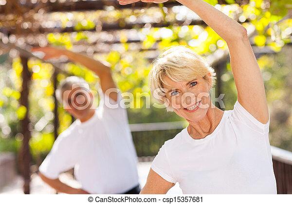 Una anciana haciendo ejercicio con su marido al aire libre - csp15357681