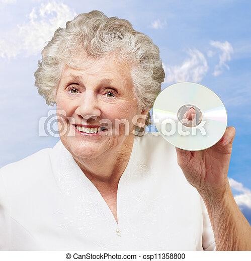 Mujer mayor sosteniendo CD - csp11358800